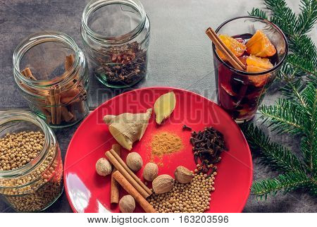 The concept of home-made mulled wine. Hot wine in clear cup with a slice of orange. Set of spices: cinnamon nutmeg cloves ginger.