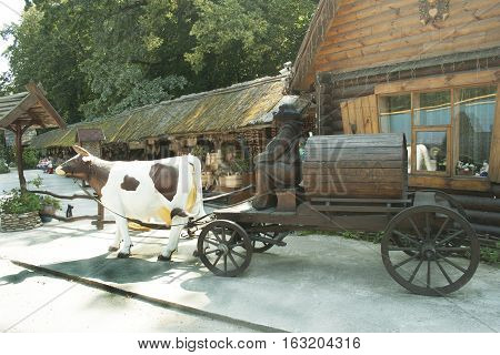 Sculpture. Old wagon. monk carries a barrel of wine in harness cow.