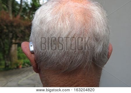 Back View Of The Head Of A Bald Man With A Hearing Aid For The Deaf Or Hard Of Hearing