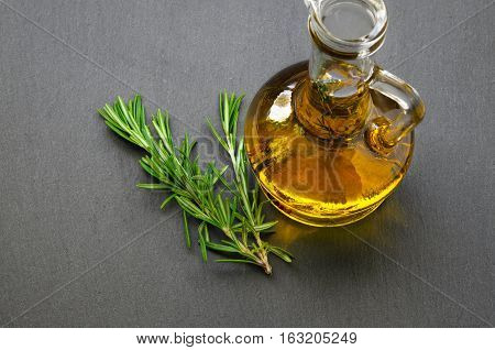 Glass bottle of olive oil, fresh rosemary branch on black slate stone surface