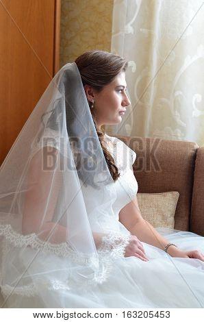 Bride in veil sitting in the chair sideways.