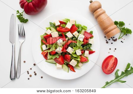 Restaurant serving of greek salad with cutlery flat lay. Top view on plate with side dish of fresh salad and feta cheese. Healthy food, vegetarian cuisine, menu, mediterranean meal concept