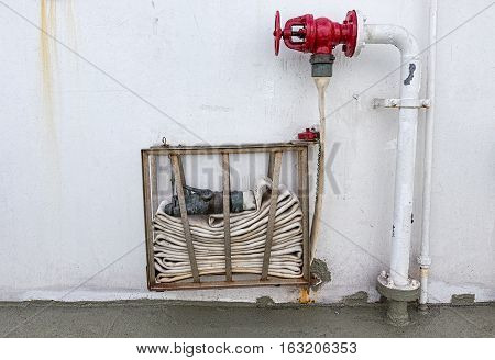 A coiled Fire Hose on a wall