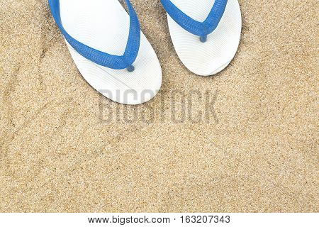 White slippers on a background of sand on the beach