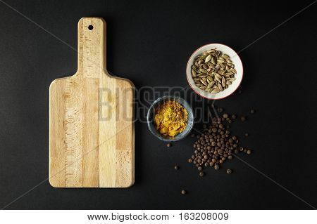 Cutting board with bowls with tumeric cardamom on black background. Space for text