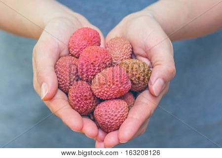 Lychee, lychees, lechee, lischi lichen fruits. Woman hands holding fresh fruits colorful vibrant purple, pink, orange and green colors. Concept for exotic superfood nutrition healthy living lifestyle