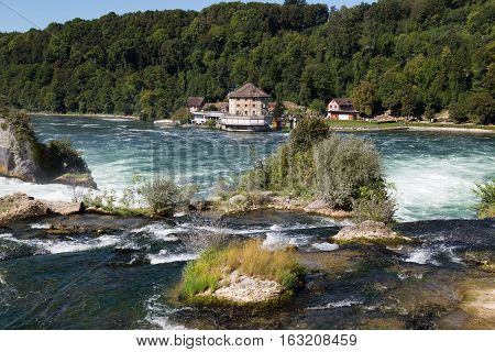 Waterfall on the river Rhine Schaffhausen Switzerland. The Rhine Falls is the largest waterfall in Europe in the summer day against the blue sky