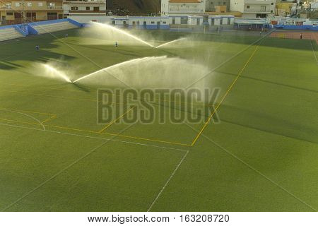 Water jets sprinkling a football field in sunny day Tenerife Spain