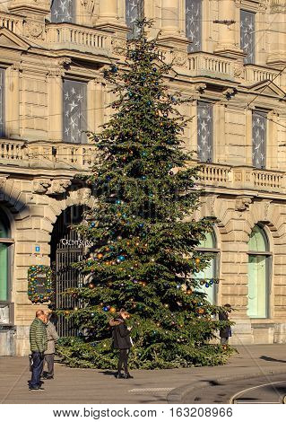 Zurich, Switzerland - 27 December, 2016: people and Christmas tree on Paradeplatz square, Credit Suisse bank office building in the background. Zurich is the largest city in Switzerland and the capital of the Swiss Canton of Zurich.