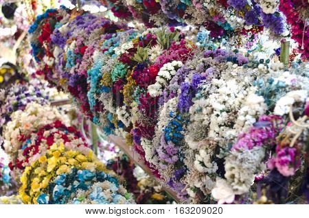 Horizontal photo in color and shallow depth of field about a lot of crowns made of colorful flowers