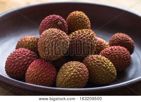 Healthy eating. Several lychee in an earthenware plate.