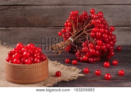 viburnum berries in a bowl on a wooden background with sackcloth.