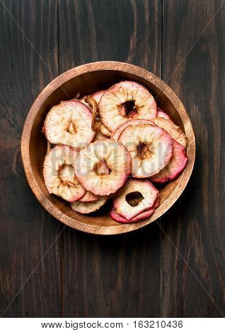 Dehydrated apples chips in wooden bowl on wooden background top view