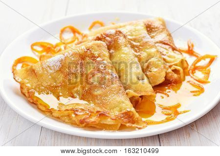 Pancakes with orange syrup on white wooden table
