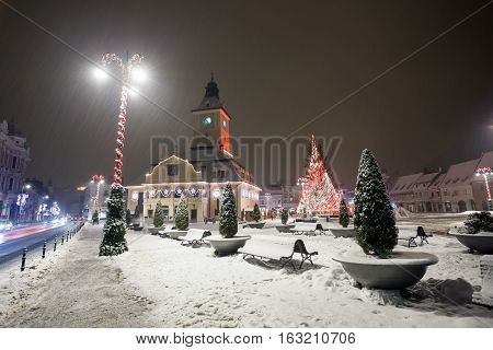 Brasov Council House night view decorated for Christmas and traditional winter market in the old town center Romania