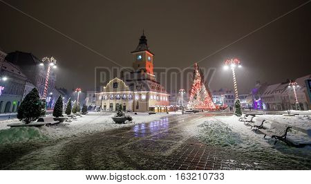 Brasov Council House night view with Christmas Tree decorated and traditional winter market in the old town center Romania