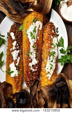Roasted corn with green herbs and sauce top view