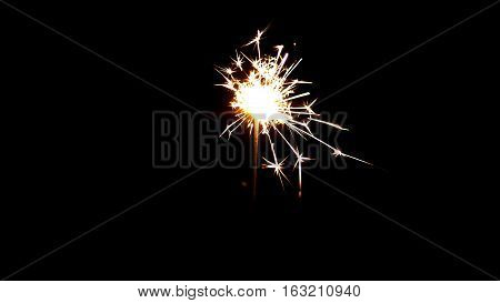Bengal fire on black background with sparks