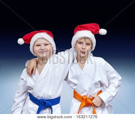 Boys in caps of Santa Claus on a gradient background