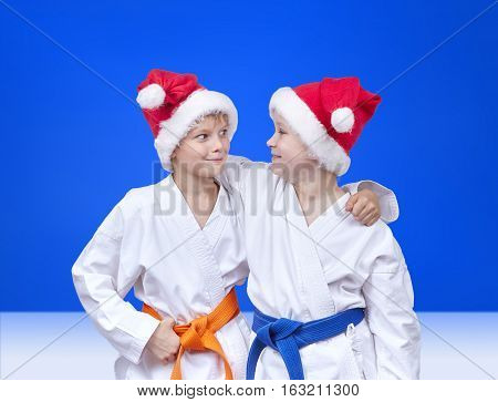 Two friends in caps of Santa Claus on a blue background