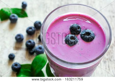 glass of fresh homemade berry smoothie and ripe berries on white wooden background. shallow depth of field. close up