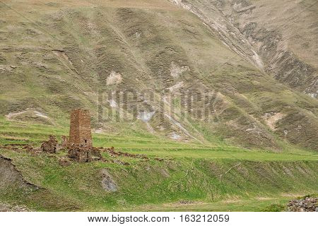 Ancient Old Stone Watchtower On Mountain Background In Chetoyta Zakagori Village, Kazbegi District, Mtskheta-Mtianeti Region, Georgia. Spring, Summer Season. Truso Gorge.