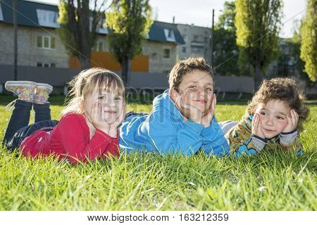 Two funny little girl and a smiling boy in the park on the spring grass lie.
