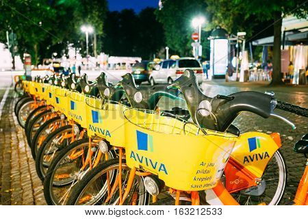 Vilnius, Lithuania - July 8, 2016: Row Of Colorful Bicycles Aviva For Rent At The Lit Municipal Bike Parking On Wet Cobblestone Of Pilies Street, Popular Showplace Of Old Town In Summer Night.
