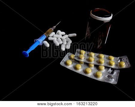 Medical pills and injection on black background