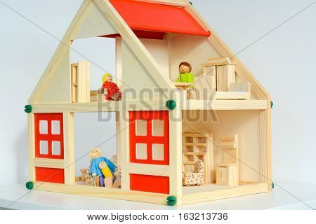 Girls dollhouse with small furniture isolated on white background