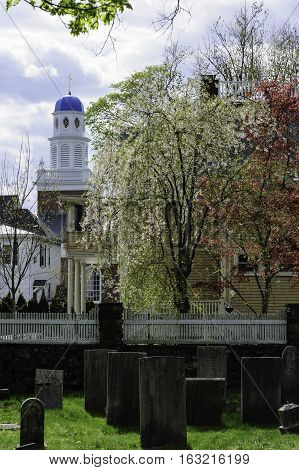 Lexington Massachusetts USA - April 20 2010: Old Burying Ground in Lexington Massachusetts with St. Brigid Parish in background
