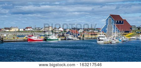 Newfoundland fishing villages see boats at rest for the day on calm coastal water.