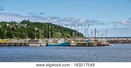 Newfoundland fishing villages see boats at rest for the day on calm coastal water.   Man unloads his truck on the dock.