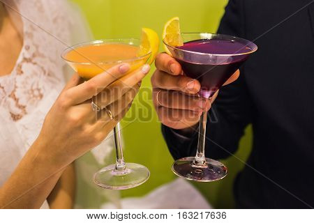 bride and groom holding glasses with cocktails orange and purple cocktail