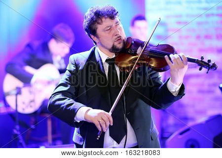 Young elegant man violinist plays the violin on a concert venue background showing emotions and face expressions.Lifestylemusic passionmusic concert