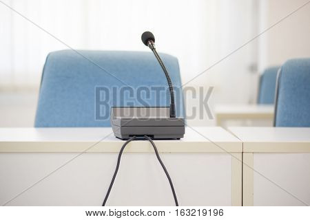 Selective focus photo of microphone on table in conference room