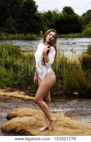 Caucasian Teen Girl At River In White Leotards With Eyes Closed