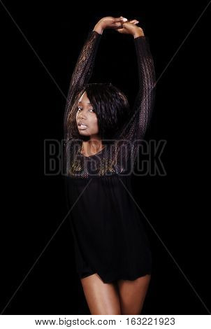 Attractive African American Woman In Black Nightie On Dark Background Standing With Arms Up