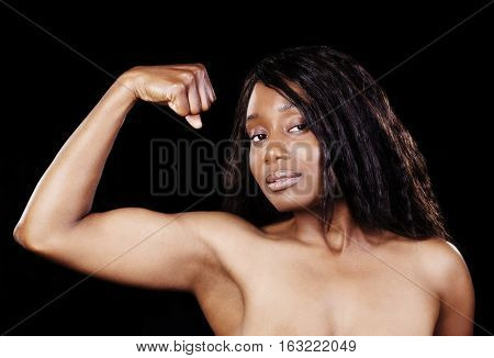 Bare Shoulders African American Woman Showing Bicep Muscle In One Arm Against Black Background