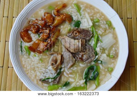 soft boiled rice with pork entrails on bowl