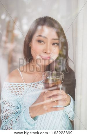 Portrait Of A Gorgeous Young Asian Woman Relaxing With Cup Of Hot Beverage Looking Throught Window.
