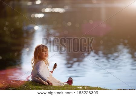 Little girl holding a bird feather and sneezes. Medical concept.