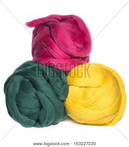 Three skeins of merino wool green, pink and yellow color on a white background