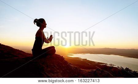 Silhouette Woman With Yoga Posture On The Mountain At Sunset.