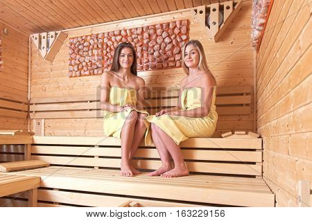Beautiful young girlfriends get together to relax in the spa. A relaxing sauna bath.