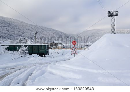 railway crossing in the village on a background of forest hills in the winter time early in the morning