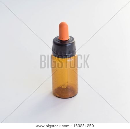 dropper and Brown glass bottles on background.