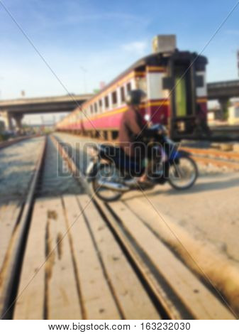Blurred Man driving motorcycle crossing railroad risk when crossing rails.