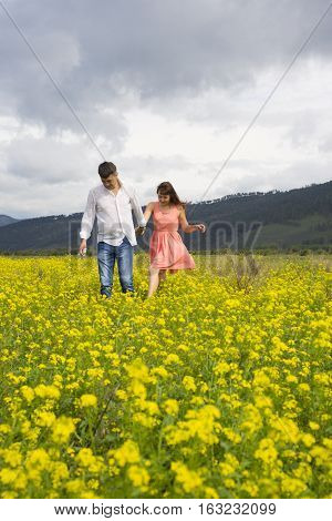 Lovers Man And Woman Walk On The Flower Field.