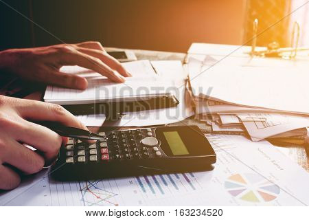 Close up man doing finance and using calculator in home office.